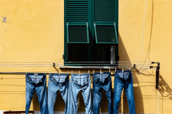 Jeans hanging to dry outside a window.