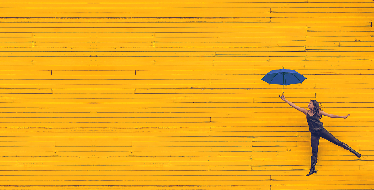 A young women leaping lightly with a blue umbrella in her hand in front of a yellow wall.