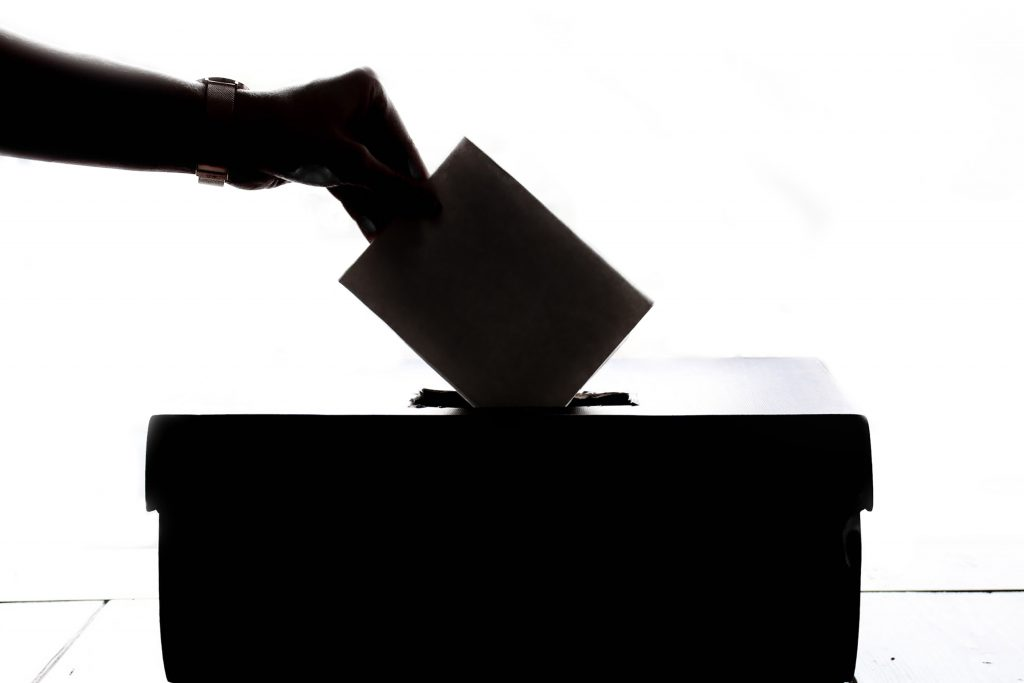 A hand dropping a ballot into a ballot box.