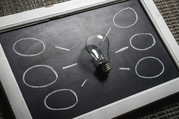 A lightbulb centered on a handheld chalkboard with empty circular thought bubbles branching off of it.