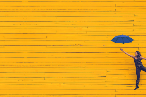 woman with umbrella on yellow background