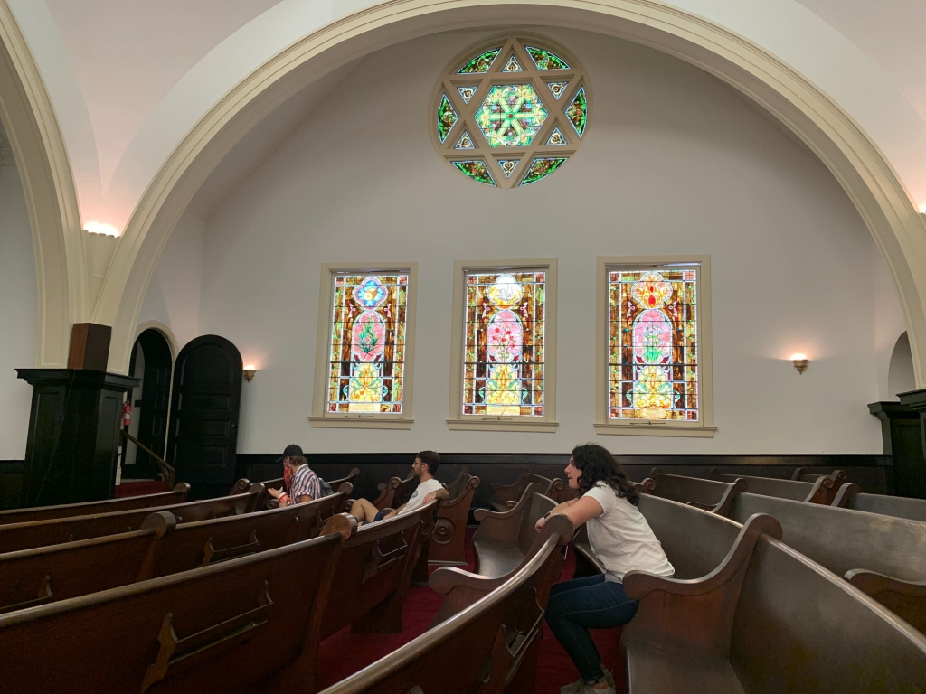 VFA Fellows: Ben, Edan, and Hailey sit in the wooden pews of Temple Mishkan Israel. They're staggered in different rows and distanced without their masks on. In the background, a stain glass Star of David sits high on the wall with three rectangular stain glass panes below it.