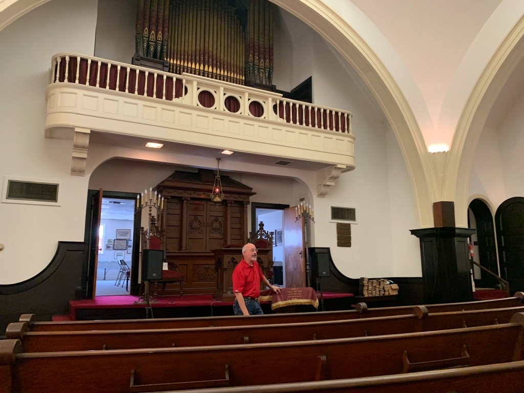 Ronnie of Temple Mishkan Israel stands at the front of the temple overlooking the rows of brown pews. Behind, is a balcony that overlooks the temple.